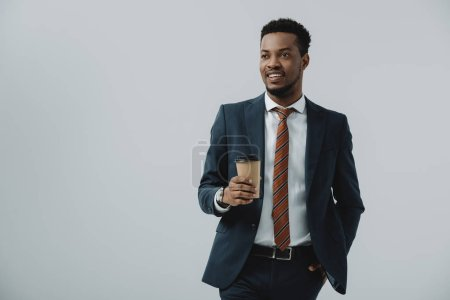 happy african american businessman holding paper cup isolated on grey