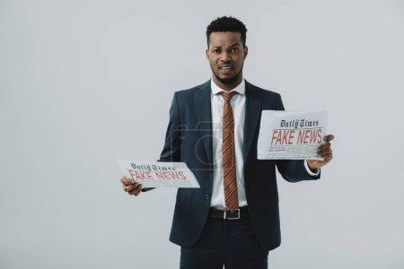 Photo pour Homme d'affaires africain américain émotif lisant le journal avec de fausses nouvelles d'isolement sur le gris - image libre de droit