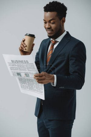 Photo for Cheerful african american man reading business newspaper and holding paper cup isolated on grey - Royalty Free Image