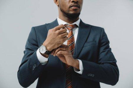 Photo pour Vue recadrée de l'homme afro-américain touchant montre isolée sur gris - image libre de droit