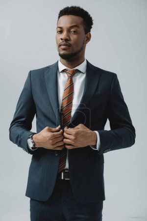 african american man touching suit isolated on grey