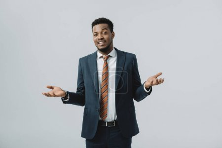 Photo for Happy african american man showing shrug gesture isolated on grey - Royalty Free Image