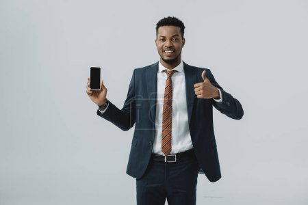 happy african american businessman showing thumb up and holding smartphone with blank screen isolated on grey