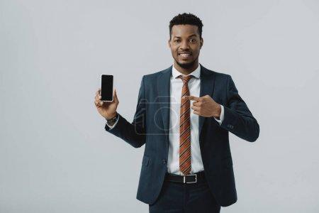 Photo pour Heureux homme d'affaires afro-américain pointant du doigt le smartphone avec écran vide isolé sur gris - image libre de droit
