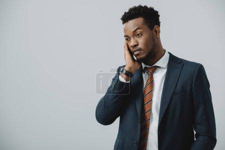 Photo pour Bel homme d'affaires afro-américain touchant visage isolé sur gris - image libre de droit