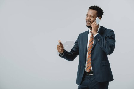 Photo for Happy african american businessman showing thumb up and talking on smartphone isolated on grey - Royalty Free Image