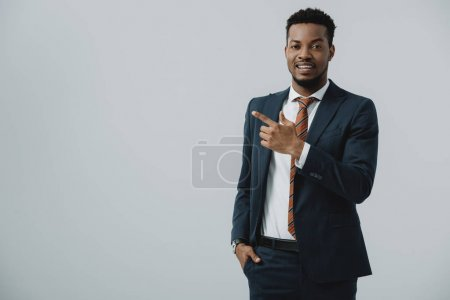happy african american man pointing with finger isolated on grey