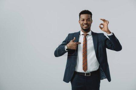 Photo pour Heureux homme afro-américain pointant du doigt ok signe isolé sur gris - image libre de droit