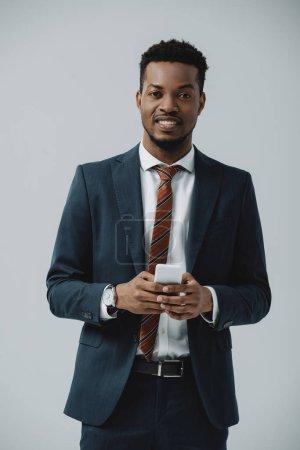 Photo pour Homme afro-américain positif en costume en utilisant un smartphone isolé sur gris - image libre de droit