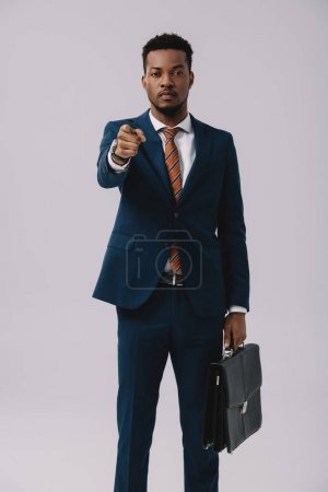 selective focus of african american man pointing with finger while holding briefcase isolated on grey