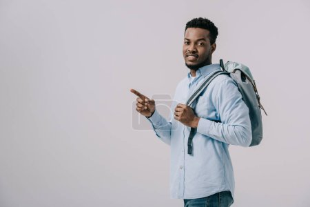 cheerful african american man with backpack pointing with finger isolated on grey