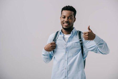 Photo pour Homme afro-américain joyeux avec sac à dos montrant pouce vers le haut isolé sur gris - image libre de droit