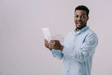 excited african american man holding digital tablet  isolated on grey