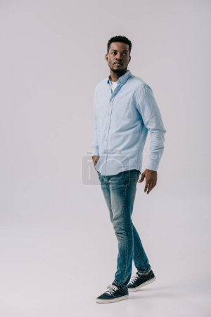 serious african american man standing with hand in pocket on grey