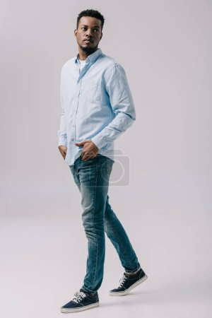 Photo for Handsome african american man walking with hands in pockets on grey - Royalty Free Image