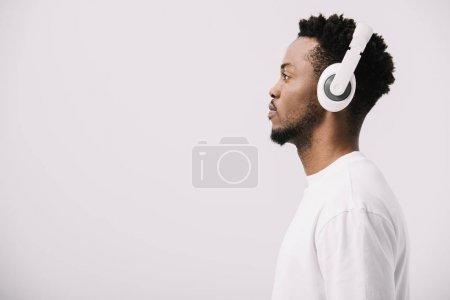 Photo pour Vue latérale de l'homme afro-américain écoutant de la musique dans les écouteurs sur blanc - image libre de droit