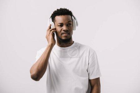 Foto de Hombre afroamericano escuchando música mientras toca auriculares aislados en blanco - Imagen libre de derechos