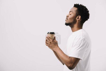 Photo pour Vue latérale de heureux homme afro-américain tenant tasse en papier isolé sur blanc - image libre de droit