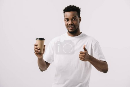 Photo for Happy african american man holding paper cup and showing thumb up isolated on white - Royalty Free Image