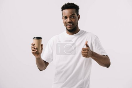 cheerful african american man holding paper cup and showing thumb up isolated on white