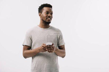 Photo pour Heureux et bouclé homme afro-américain en utilisant smartphone isolé sur blanc - image libre de droit