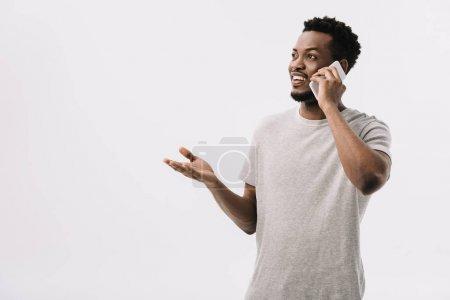 Foto de Hombre afroamericano feliz gesturing mientras se habla en teléfono inteligente aislado en blanco - Imagen libre de derechos
