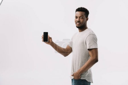 hombre afroamericano guapo de pie con la mano en el bolsillo y la celebración de teléfono inteligente con pantalla en blanco