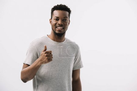 positive african american man showing thumb up while looking at camera isolated on white