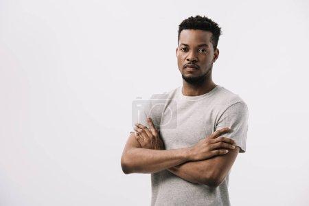 Photo pour Homme américain africain bouclé restant avec les bras croisés tout en regardant la caméra d'isolement sur le blanc - image libre de droit