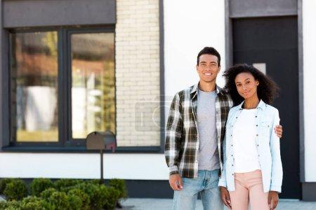 Photo pour Mari et femme afro-américains restant près de la nouvelle maison et regardant l'appareil-photo - image libre de droit