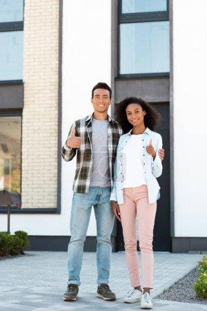 volle Länge Ansicht der afrikanisch-amerikanischen Mann und Frau zeigt Daumen nach oben, während sie in der Nähe des neuen Hauses stehen und in die Kamera schauen