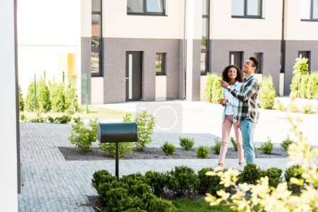 Photo for Full length view of african american man and woman standing near house while husband pointing with finger - Royalty Free Image