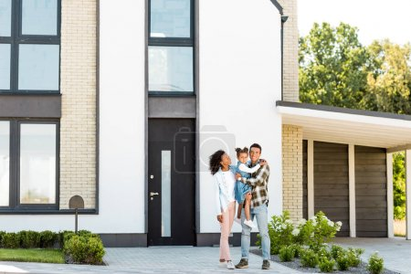 Photo for Full length view of african american family standing near new house while father holding kid - Royalty Free Image