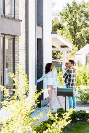 Photo pour Vue pleine longueur de la mère américaine africaine ouvrant la porte de la nouvelle maison tandis que le père retenant le gosse - image libre de droit