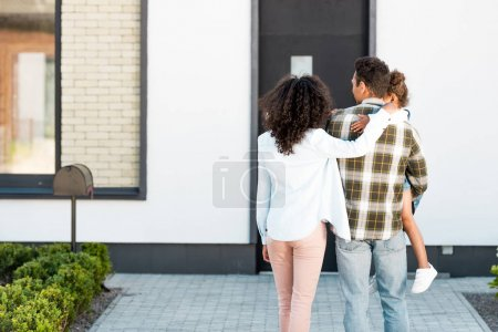 Photo for Back view of father holding kid and mother hugging husband - Royalty Free Image