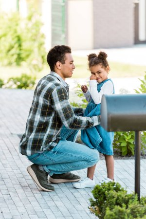 Photo for Full length view of african american father talking to daughter while kid smiling and looking away - Royalty Free Image