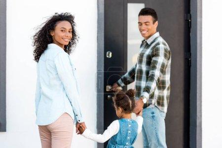 Photo pour Famille restant près de la nouvelle maison tandis que le père retenant des mains avec l'enfant et la mère regardant l'appareil-photo - image libre de droit