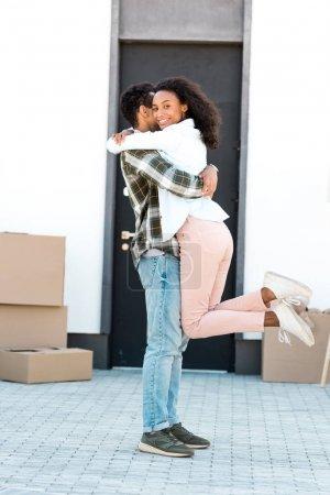 Photo pour Vue pleine longueur du mari américain africain retenant la femme dans la main tandis que la femme regardant l'appareil-photo - image libre de droit