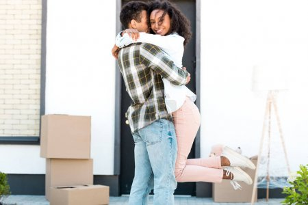 Photo pour Africain américain mari étreignant femme tout en tenant femme dans les mains et fille regardant caméra - image libre de droit
