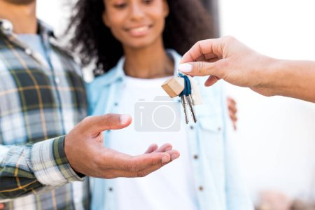 Photo for Cropped view of african american woman giving key of new house to happy couple - Royalty Free Image