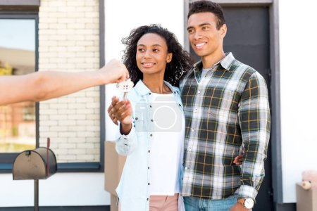 Photo for African american couple looking at woman and smiling while taking key of new house - Royalty Free Image
