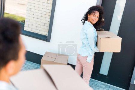 Photo pour Foyer sélectif de la femme afro-américaine regardant mari tout en tenant boîte - image libre de droit