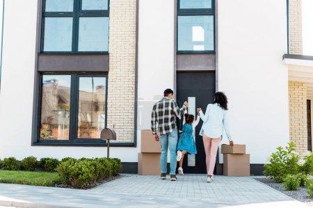 Photo pour Vue pleine longueur des parents américains africains retenant des mains avec l'enfant et marchant à la nouvelle maison - image libre de droit