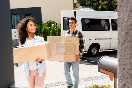 Photo pour Foyer sélectif des boîtes de fixation de couples américains africains tout en marchant dans la maison - image libre de droit