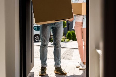 Photo for Cropped view of man and woman holding boxes while walking into house - Royalty Free Image