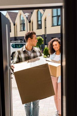 Photo pour Afro-américaine femme et homme tenant en boîte tout en se regardant et entrant dans la maison - image libre de droit