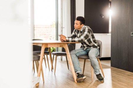 Photo pour Vue pleine longueur de bel homme afro-américain assis devant la table et utilisant un smartphone - image libre de droit