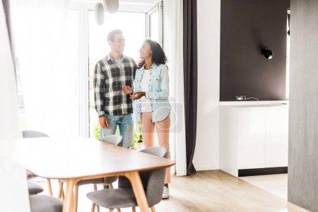Photo pour Vue pleine longueur de mari et femme afro-américains marchant dans la maison tout en regardant les uns les autres - image libre de droit