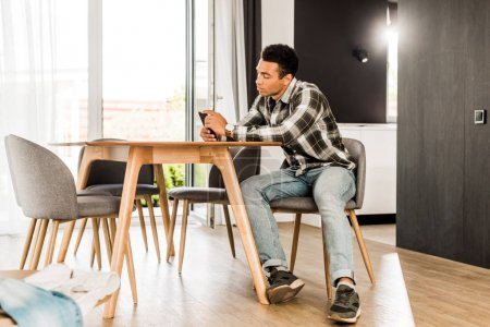 Photo pour Vue pleine longueur de l'homme afro-américain assis devant la table et utilisant un smartphone - image libre de droit