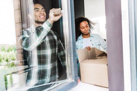 Photo pour Fenêtre d'ouverture afro-américaine de mari tandis que la boîte d'ouverture de femme - image libre de droit